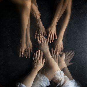 Tason päällä olevia käsiä, joista osa koskettaa toisiaan.