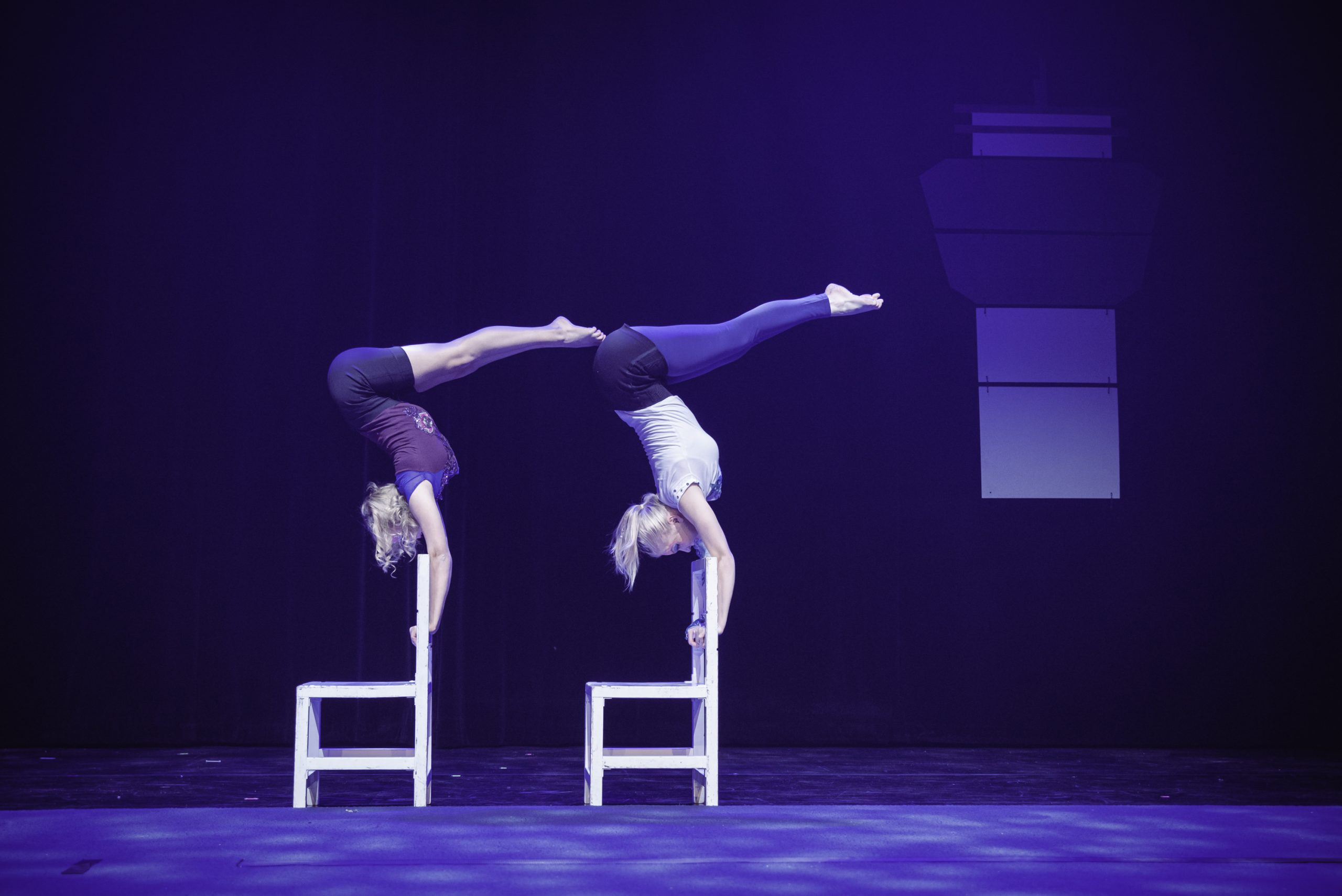 Kuvassa kaksi sirkustaiteilijaa seisoo käsillään tuolien selkänojilla. Heidän kehonsa alavartalonsa on yhdeksänkymmenen asteen kulmassa ylävartaloon nähden.